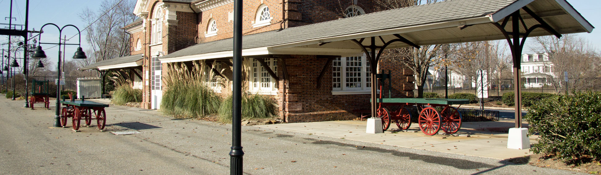 Close-up photo of corner of train station building with old metal cart in photo